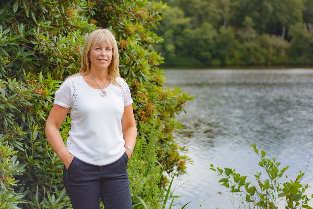 Suzanne Pullen - the inner potential - suzanne standing by a lake with her hands in her pockets